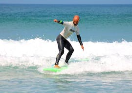 A participant of the Surfing Lessons on the Costa Vicentina with Pick-Up is learning how to surf in the Algarve with the help of an instructor from Neptunos Surf School Algarve.