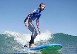 A surfer is happy to stand on her surfboard thanks to her surfing lessons on the Marinella Beach, with the ESCF Anglet - Seignose surf school.