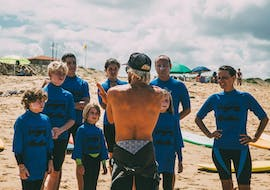 A surf instructor from the surf school ESCF Anglet - Seignosse is giving instructions for the participants of the surfing lessons on the Bourdaines Beach.