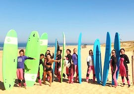A group of surfers is posing for a photo with their boards planted in the sand next to them during their Surfing Lessons - Culs Nus Beach - All Levels with Hossegor Surf Center.