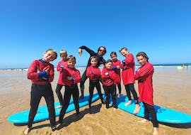 A group of kids is posing for a picture with their surfing instructor during their Surfing Lessons on the Sablères Beach with the surf school ESCF Vieux Boucau.