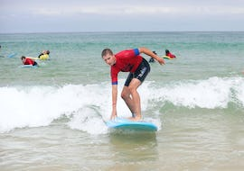 A surfer is taking a small wave on the shore thanks to his surfing lessons on the Penon Beach with ESCF Hossegor surf school.