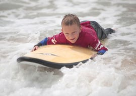 A surfer is lying on his surfboard and sliding on whitewhater during his surfing lessons on the Penon beach with the ESCF Anglet - Seignosse surf school.
