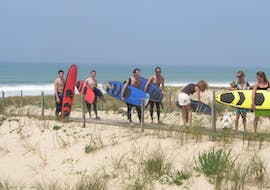 7 young people with their surfboards make the surfing lesson for all levels on the sail fish beach with nomad surf school.