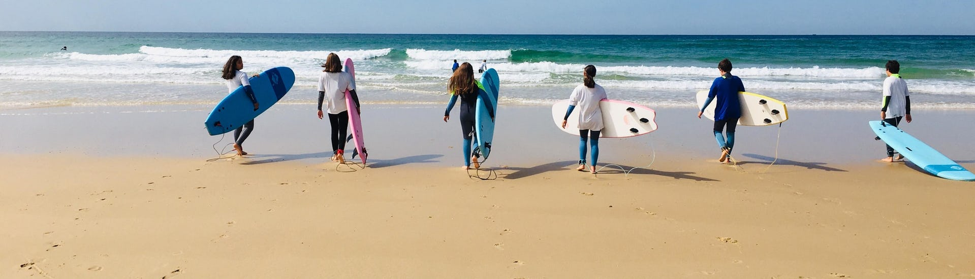 A group of students is going to the see to have their Surfing Lessons for All Levels from 8 years with It's On Surf School.