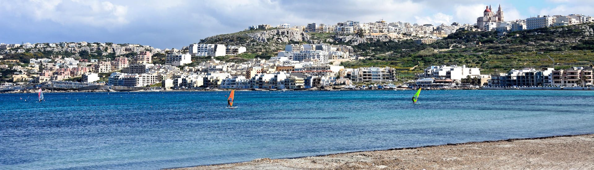 A young woman surfing in the clear blue waters of the surfing and SUP hotspot of Malta.