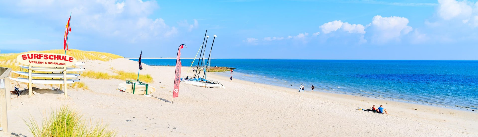 A young woman surfing in the clear blue waters of the surfing and SUP hotspot of Sylt.