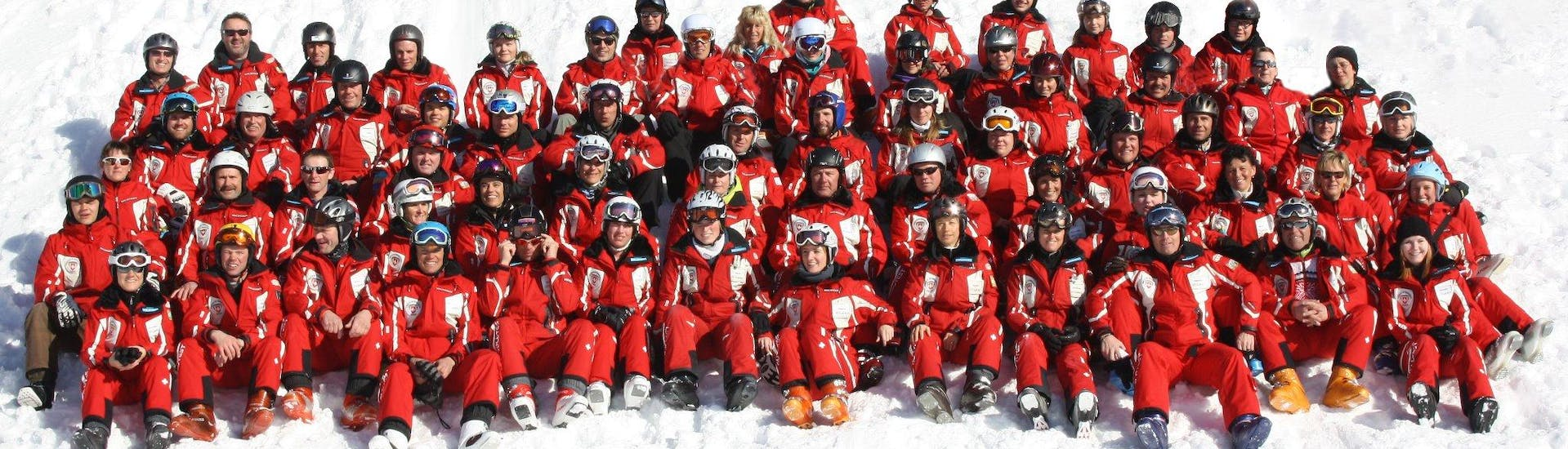 The whole team of ski and snowboard instructors of Swiss Ski School Wildhaus is taking a group picture together.