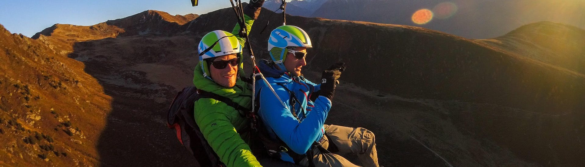 During the Tandem Paragliding from Monte Spico at Sunrise, a tandem pilot and his passenger are enjoying the calm flight in the early morning.