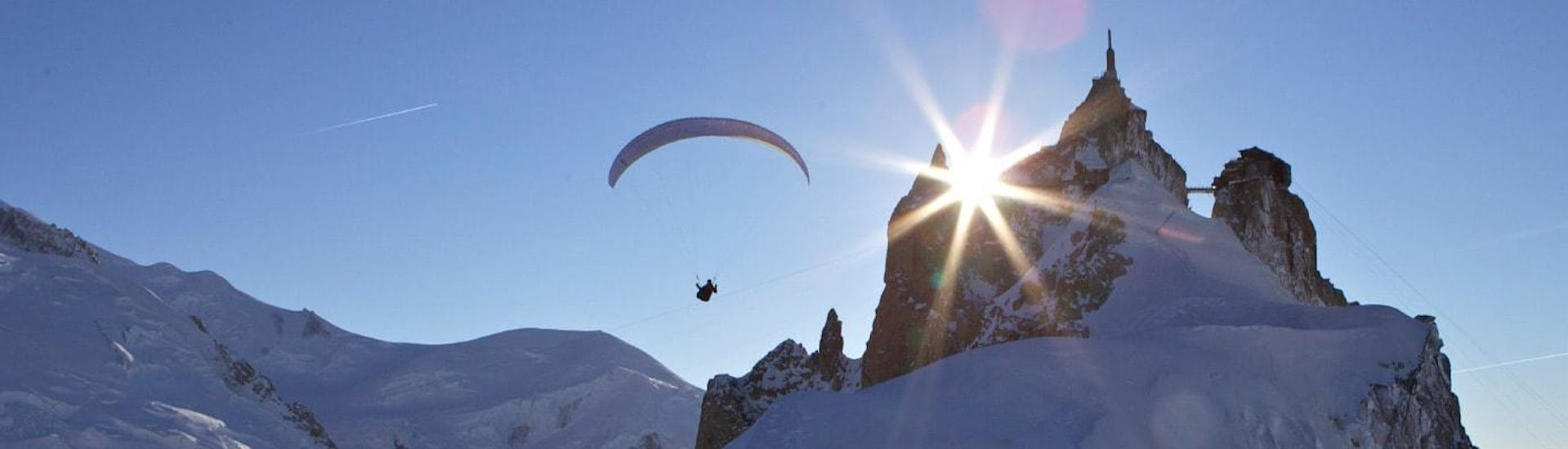 A paragliding pilot from Kailash Paragliding is doing a Tandem Paragliding Flight from the Aiguille du midi against a mountain backdrop.