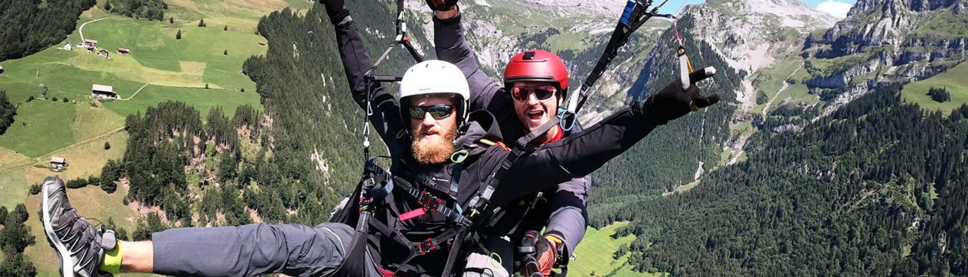 A young man and his tandem pilot from Mountain O'Clock are smiling at the camera while paragliding at Lake Lucerne.