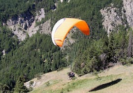 A paragliding pilot from Emotion'Air is doing a Tandem Paragliding Discovery Flight from the Col du Galibier.