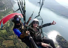 """A paragliding pilot from Takamaka Aix Les Bains is taking a participant flying above the Lac du Bourget during a Tandem Paragliding """"Discovery""""."""