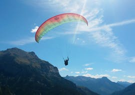 A paragliding pilot from Emotion'Air is doing a Tandem Paragliding Discovery Flight from the Col du Granon.