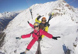 """A tandem master and his passenger are flying over snowy Swiss mountains during the activity Tandem Paragliding """"Explore"""" - Zermatt provided by Flybypara."""