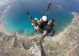 A woman is smiling into camera whilst tandem paragliding above Falasarna Beach with a certified pilot from Cretan Paragliding.