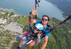 A kid is having her Tandem Paragliding at Lake Annecy for Kids (3 -12 years) activity with FRI Parapente.