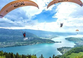 Two children are flying during their Tandem Paragliding in Lake Annecy for Kids (3-12 years) activity with Flyeo.