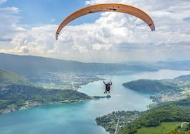 A child is flying during their Tandem Paragliding Flight in Lake Annecy for Kids (3-12 years) with Flyeo.