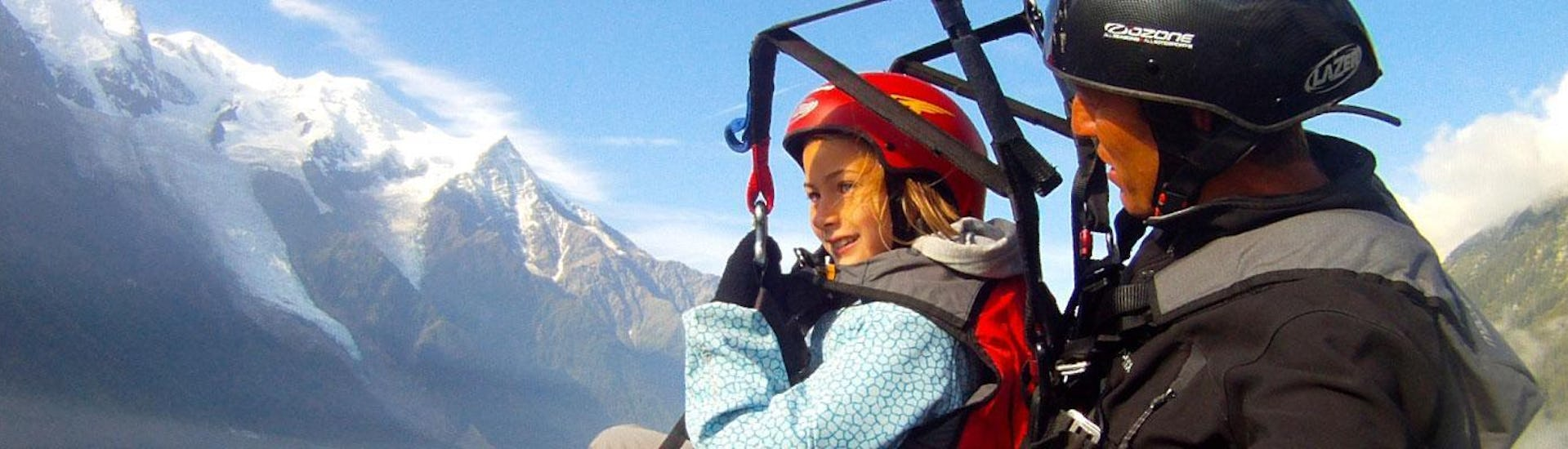 A child is enjoying their Tandem Paragliding Flight for Kids (4-12 years) with an experienced pilot from Kailash Paragliding.