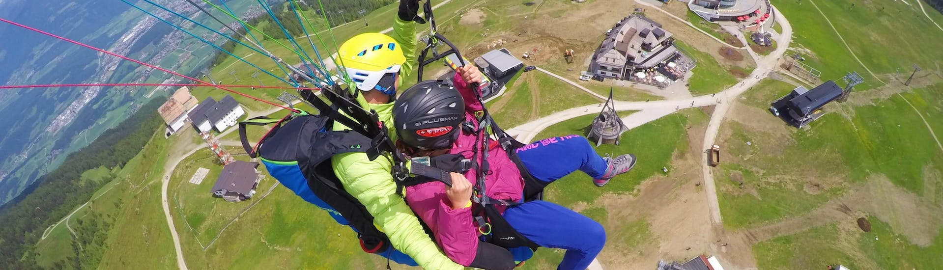 A young woman is gliding over the peak of Plan de Corones with her tandem pilot during the Tandem Paragliding from Plan de Corones with Tandemflights Kronplatz.