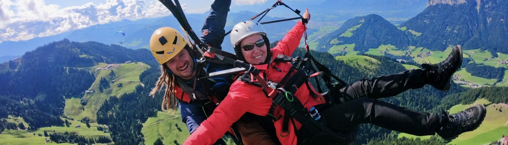 A tandem pilot from TirolAir and his passenger who has booked the Acrobatic Flight are seemingly enjoying themselves while paragliding from the Hohe Salve mountain.