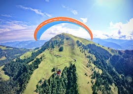 A tandem pilot from TirolAir and his passenger are gently floating over the peaks of the Kitzbühel Alps while paragliding from the Hohe Salve.