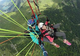 """A tandem pilot from FlyTeam and his passenger are flying over the green mountain landscape during the Tandem Paragliding """"Full Day"""" in Allgäu and Tyrol."""