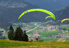 A paragliding pilot from Emotion'Air is doing a Tandem Paragliding Hand'Icare Flight from the Puy Chalvin.