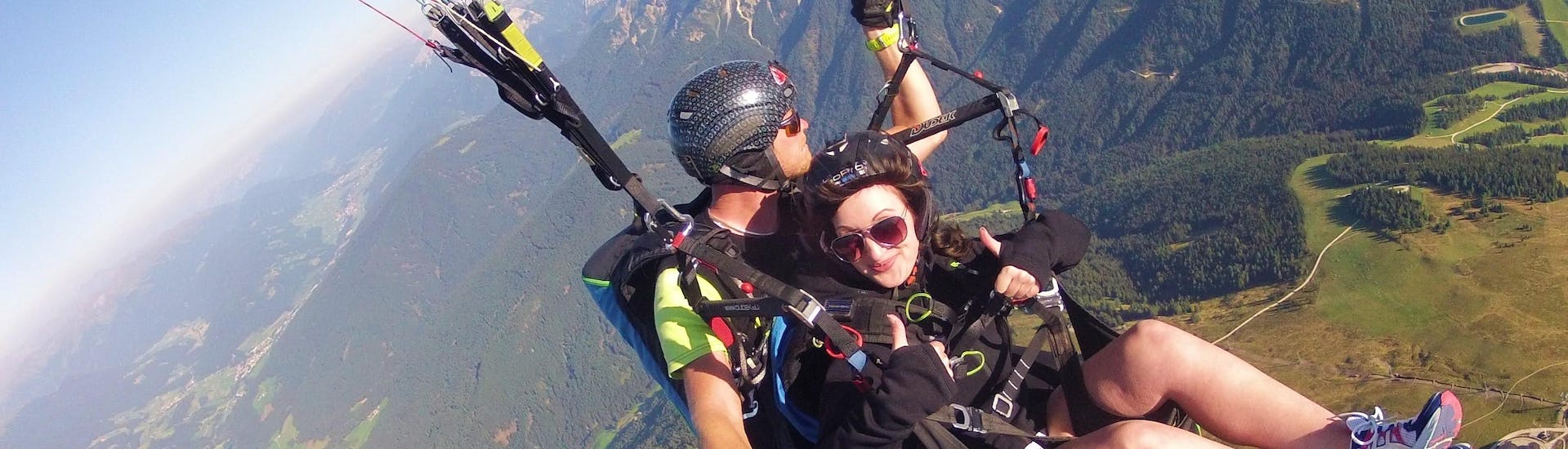 During the Tandem Paragliding in Falzes near Brunico with Tandemflights Kronplatz, a young woman and her tandem pilot are enjoying the spectacular view.