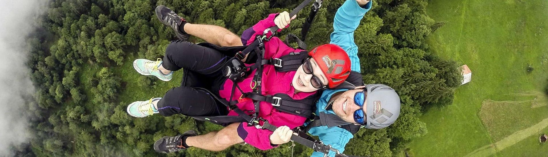 """A tandem pilot from Skywings Interlaken and his passenger are smiling at the camera as they fly across the tree tops on their Tandem Paragliding in Interlaken - """"The Thermal"""" flight."""