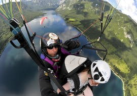 During the Tandem Paragliding in Triglav National Park from Mt. Vogar, a tandem pilot from 3glav Adventures and his passenger are gliding over Lake Bohinj.