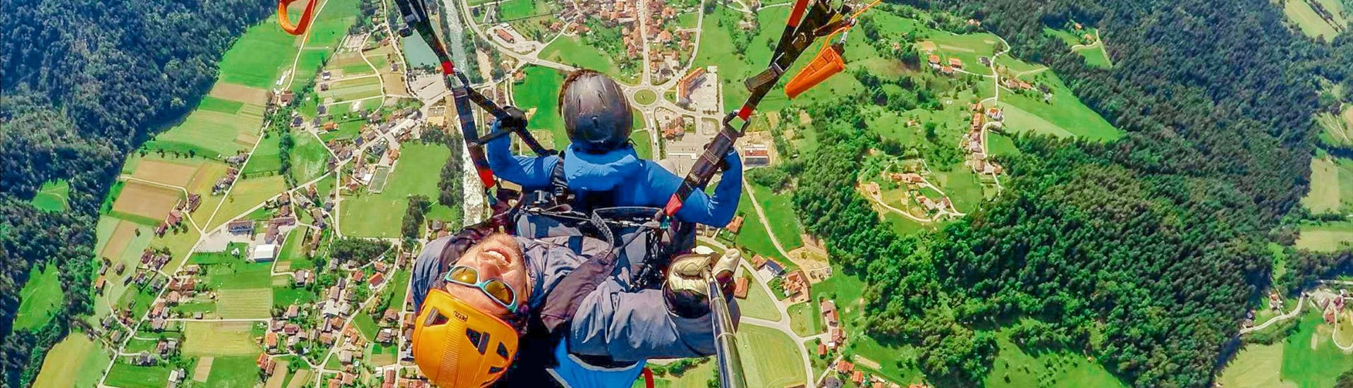 A tandem pilot from Menina Funpark and his passenger are gliding over the green landscape during the Tandem Paragliding in Upper Savinja Valley.
