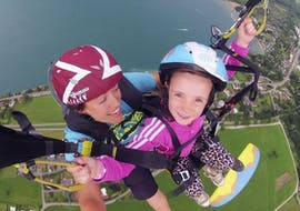 A kid is having fun during her Tandem Paragliding at Lake Annecy - Lady pilot activity with FBI Parapente.