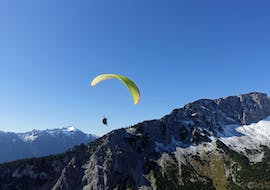 """During the Tandem Paragliding """"Long Distance Flight"""" in Allgäu and Tyrol, a paraglider from FlyTeam is soaring high above the mountains."""