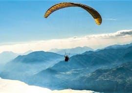 A paragliding pilot is soaring above the Garda Lake during the flight Tandem Paragliding on Lake Garda - Monte Baldo organized by GardaAirStyle.
