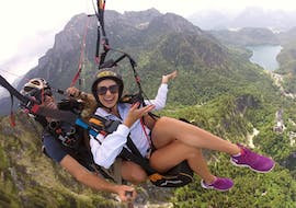 A passenger and her tandem pilot from Flugschule Aktiv are soaring high above Schwangau during the Tandem Paragliding over Neuschwanstein Castle from Tegelberg.