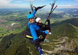 """A tandem pilot from FlyTeam and his young passenger are soaring high above the Allgäu Prealps during the Tandem Paragliding """"Panorama"""" from Breitenberg."""