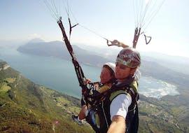 """Une participante à un vol parapente biplace """"Performance"""" avec Takamaka Aix Les Bains profite de son vol au-dessus du lac du Bourget et de ses merveilleux paysages."""