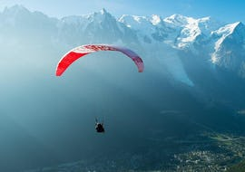 A paragliding pilot from Kailash Paragliding is doing a Tandem Paragliding Flight from Plan de l'Aiguille above the Chamonix Valley.