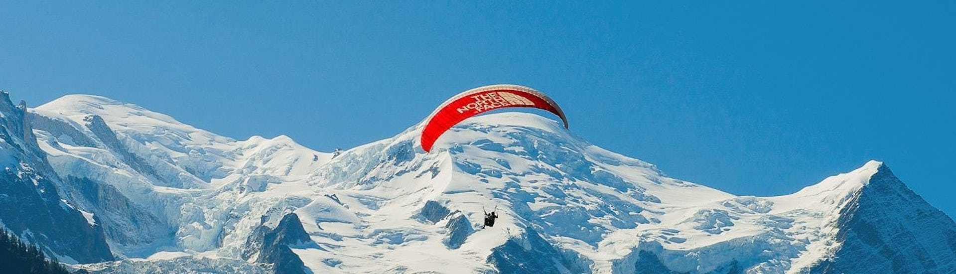 A paragliding pilot from Kailash Paragliding is flying above the mountains during a Tandem Paragliding Flight from Planpraz - Chamonix.