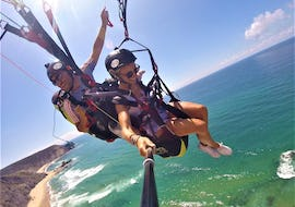A tandem pilot and his passenger are soaring over the turquoise water of the Atlantic during the Tandem Paragliding at Praia da Cordoama organized by Flytrip.