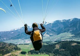 A paragliding pilot from Emotion'Air is doing a Tandem Paragliding Prestige Flight from the Col du Galibier.
