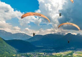 A couple of friends is flying during their Tandem Paragliding in Lake Annecy - Prestige activity with Flyeo.