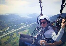 """Une participante à un vol parapente biplace """"Sensation"""" avec Takamaka Aix Les Bains profite de son vol au-dessus du lac du Bourget et de ses merveilleux paysages."""