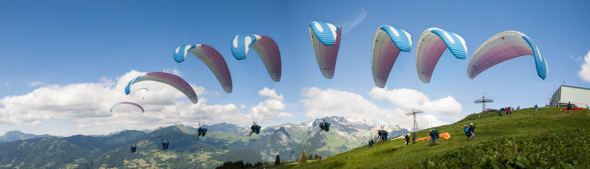 """A paragliding pilot from Pegase Air is taking off from one of the moutains surrounding Samoens for a Tandem Paragliding Flight """"Sensation""""."""