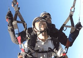 """During the Tandem Paragliding """"Sensations"""" - Puy de Dôme, a man is having great time whilst flying through the sky with his experienced pilot from Absolu Parapente."""