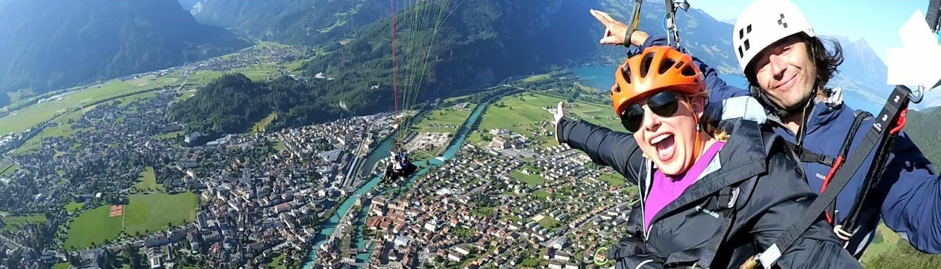 """During the Tandem Paragliding """"The Sensational"""" in  Interlaken, a certified tandem pilot from Twin Paragliding and his passenger are taking a picture while gliding over the beautiful town of Interlaken."""
