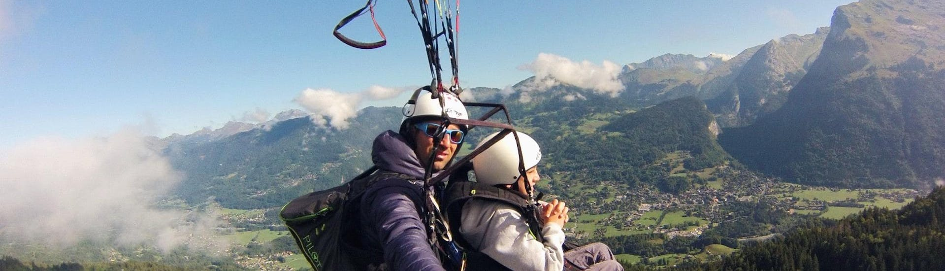 """A child makes a Tandem Paragliding flight """"Young Highlander"""" with Pegase Air over the Samoens valley."""