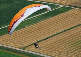 """A paragliding pilot is flying over a field during their Tandem Paragliding """"Discovery"""" - Chartreuse with Prévol Parapente."""